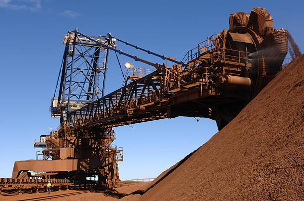 Iron ore reclaimer and iron ore stockpile stock photo