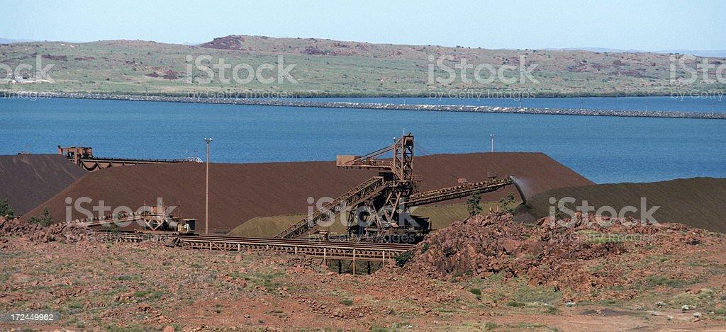Iron ore stockpile and active reclaimer royalty-free stock photo