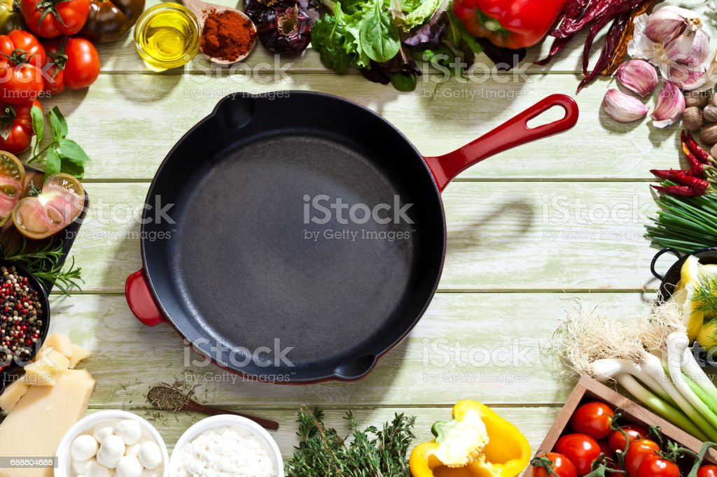 Iron pan with fresh ingredients for cooking and seasoning stock photo