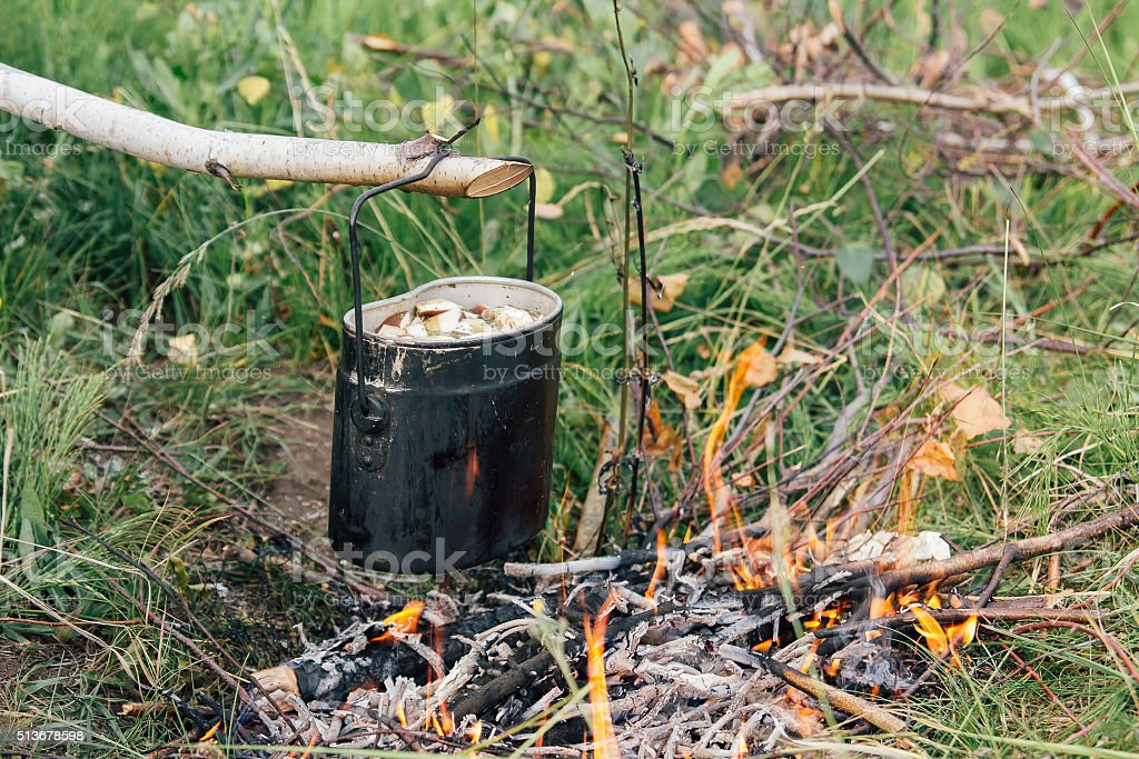 Iron pot cooks soup with mushrooms over an open fire at the campsite