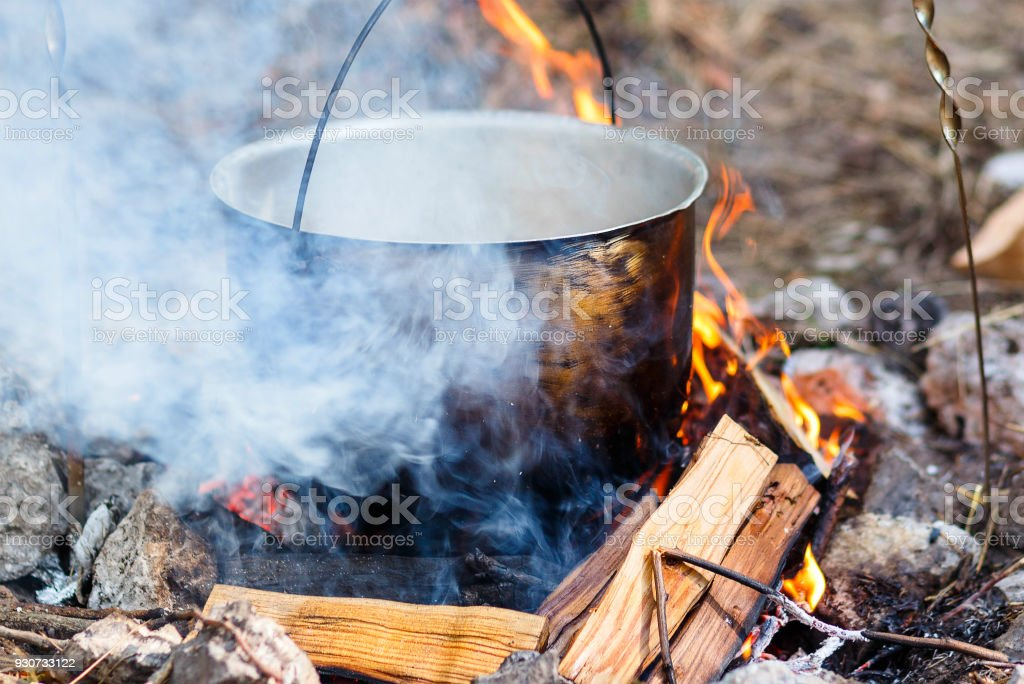 Iron pot with food on a burning fire. Food in a metal cauldron is...