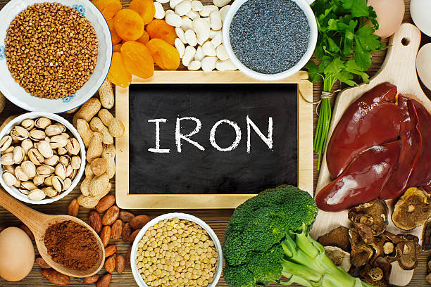 Iron rich foods Collection iron rich foods as liver, buckwheat, eggs, parsley leaves, dried apricots, cocoa, lentil, bean, blue poppy seed, broccoli, dried mushrooms, peanuts and pistachios on wooden table. theobroma stock pictures, royalty-free photos & images