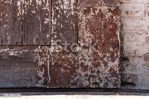 894368086 istock photo Iron rusted and unpainted angle of a wooden door with a bircks background 1081954754