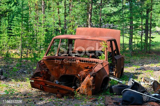 Iron rusty body of the Soviet car lies among the debris in the shade in a young spruce forest in the tundra of Yakutia.