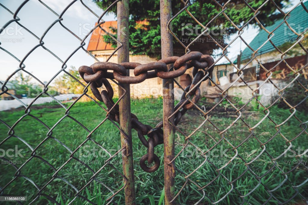 Iron Rusty Chainlink Grid Fence Rust On Metallic Locked Gate Chain With Lock Closeup Grungy Chain In Heart Shape Country House Behind Steel Mesh Fence Rustic Rough Background With Copy Space Stock