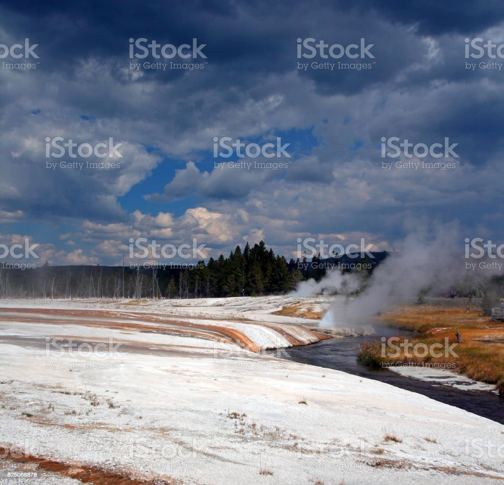 Iron Spring Creek flowing past Cliff Geyser in Black Sand Geyser Basin in Yellowstone National Park in Wyoming USA stock photo
