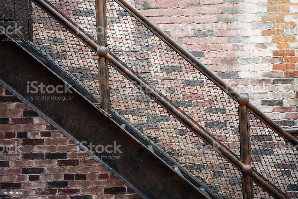 iron stairs set with patterned steps on the old brick stock photo