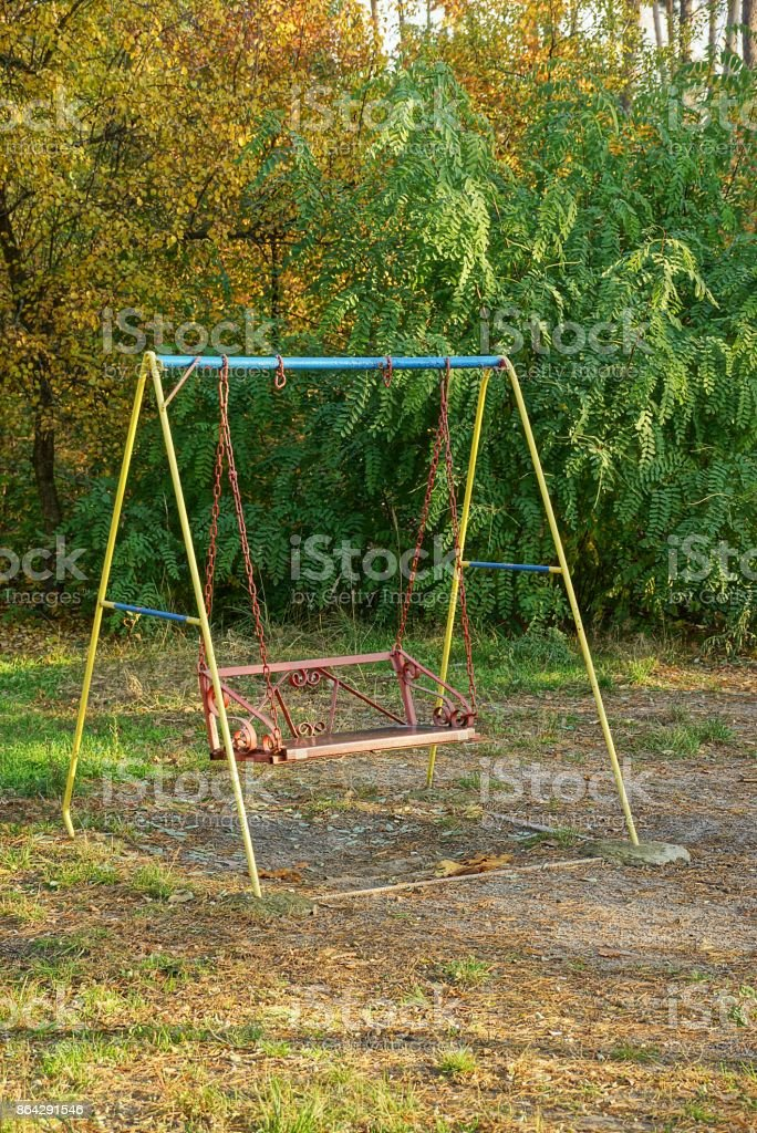 iron swing for children on a glade in the park royalty-free stock photo