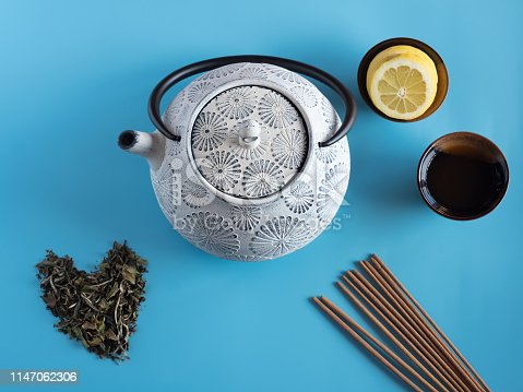 Japanese, chinese, Iron teapot painted in blue and white, white tea leaves forming a heart, cup of tea containing slices of lemon, on turquoise blue background and incense sticks. top view flat lay