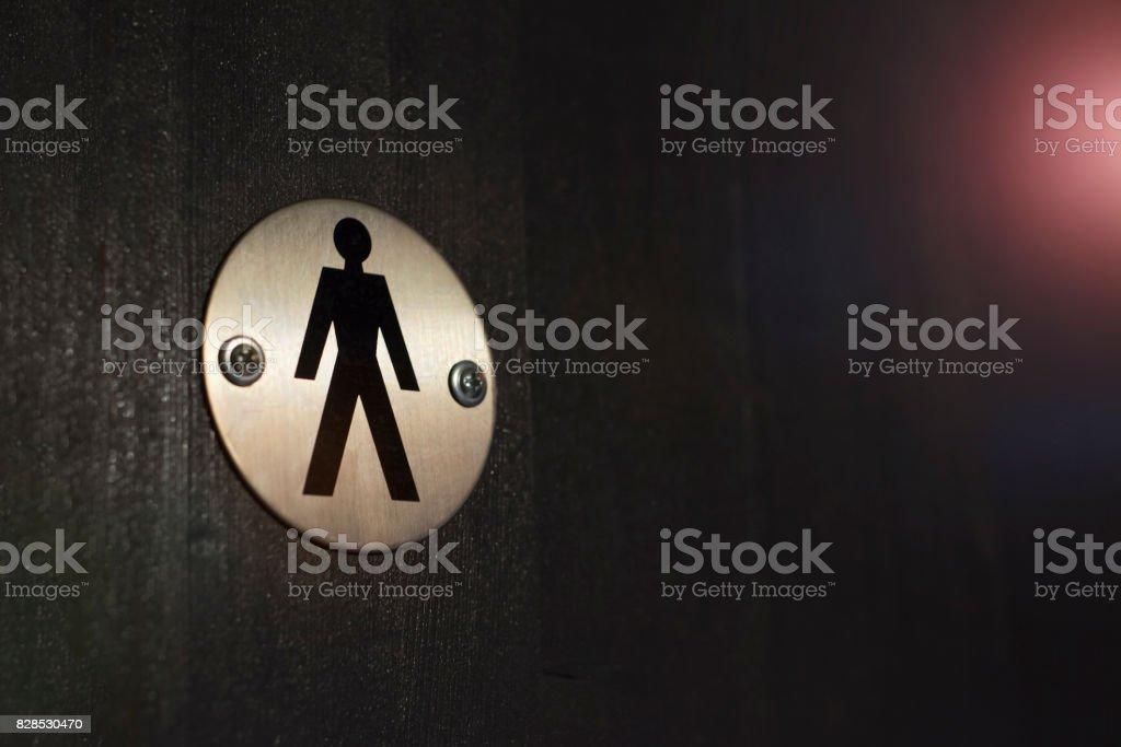 Eisen-Toilette-Logo auf dem Hintergrund der schwarzen Holzwände – Foto