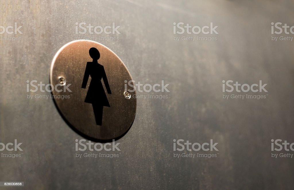 Eisen-Toilette-Logo auf dem Hintergrund der grauen Holzwände – Foto