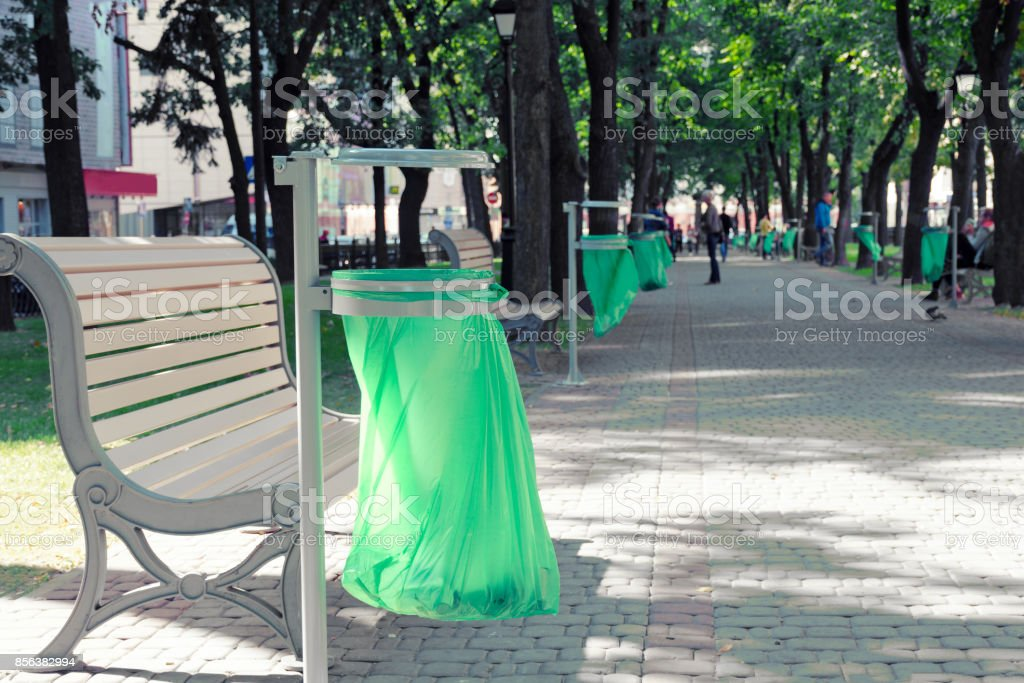Iron trash can with plastic bag in the city park. stock photo