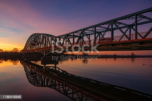 iron truss bridge at sunset