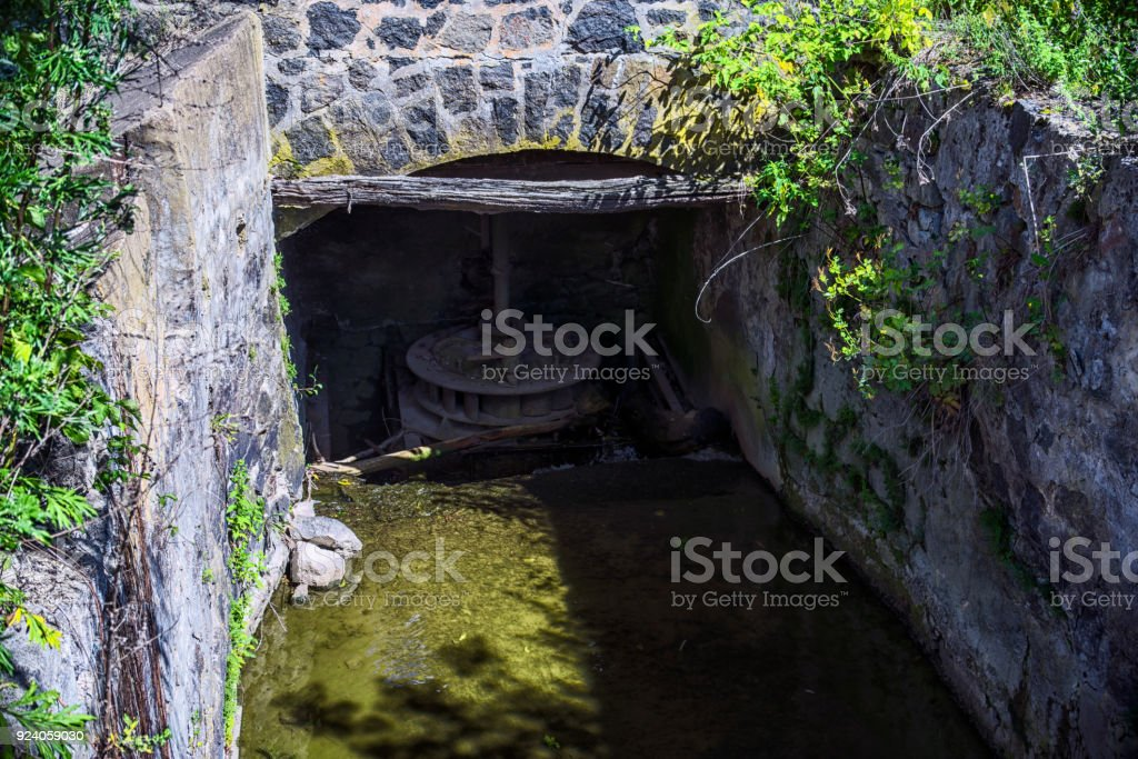Iron wheel in the shallow channel of the mill. stock photo