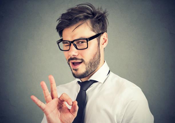 hombre irónico mostrando el gesto ok - ironía fotografías e imágenes de stock