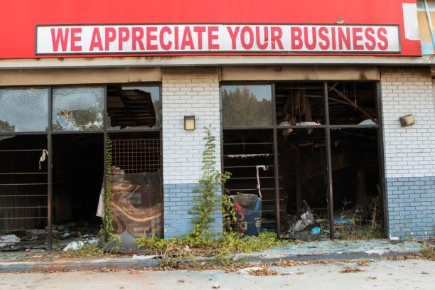signo irónico se sienta encima de quemado y destrozado pequeñas empresas - ironía fotografías e imágenes de stock