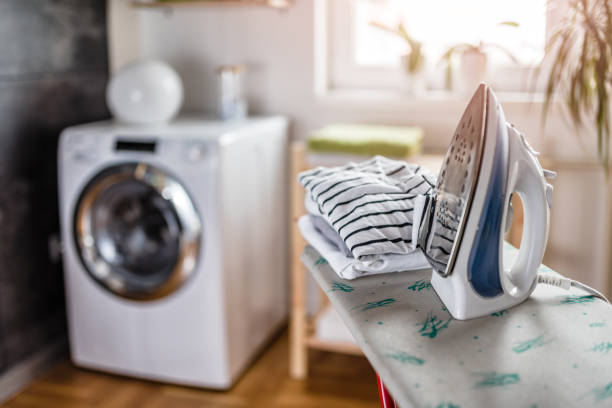 ironing in the laundry room - laundry laundry room stock pictures, royalty-free photos & images