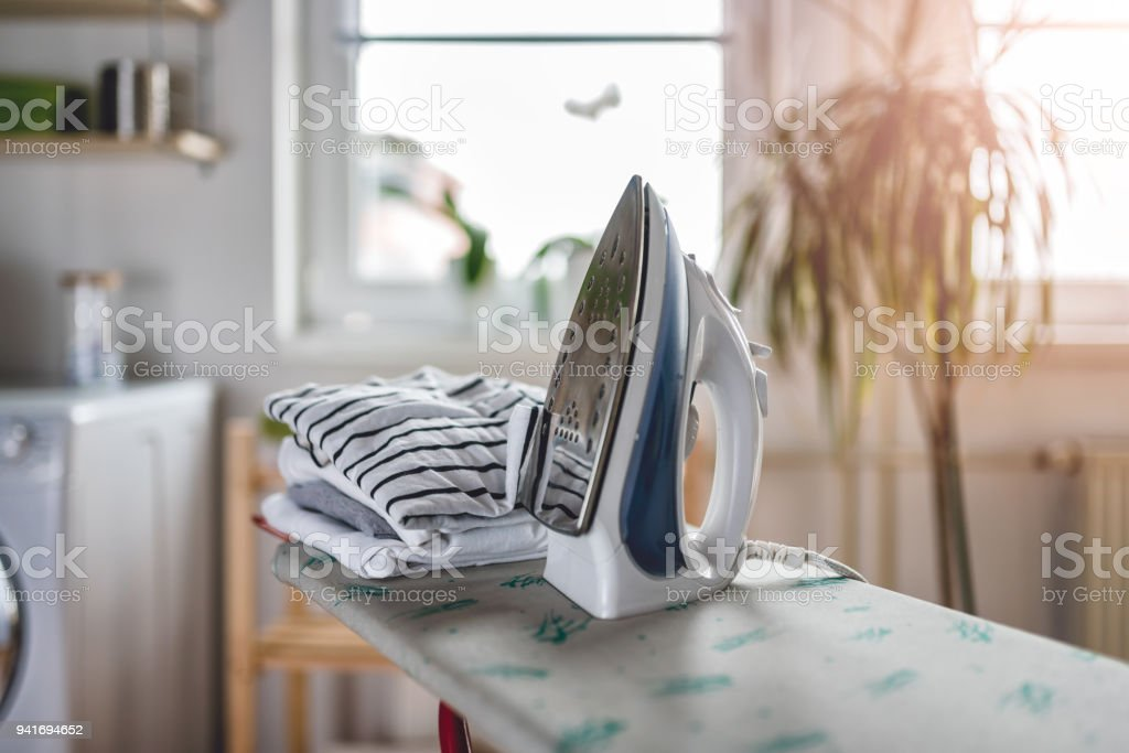 Ironing in the laundry room stock photo