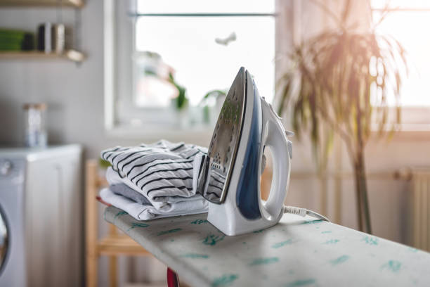 ironing in the laundry room - ironing stock photos and pictures