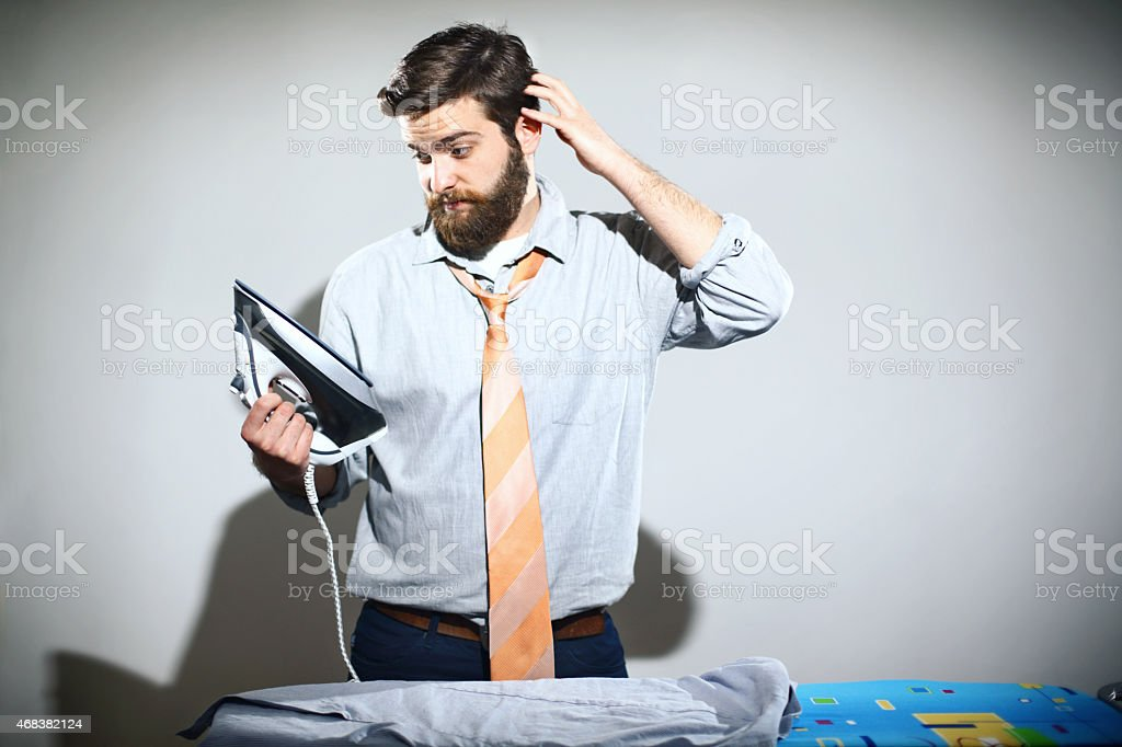 Ironing is not a man's job. stock photo