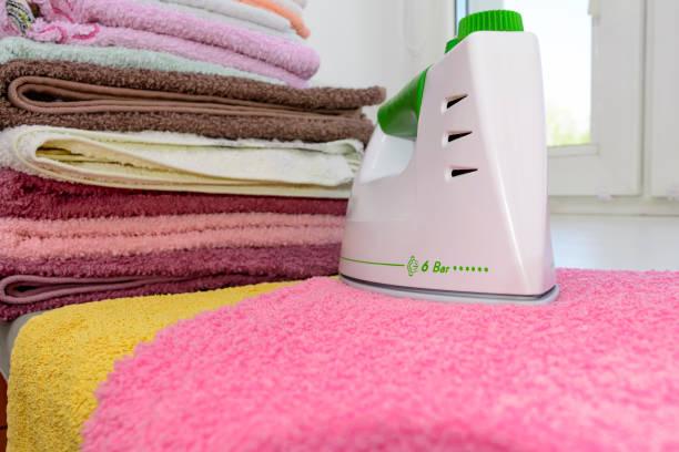 Leinen Bügeln mit Eisen. Ein Stapel gebügelt Handtücher liegen neben dem Eisen. Heiße Eisen auf dem Bügelbrett. Teflon-Bügelsohle bedeckt mit kleinen Löchern – Foto