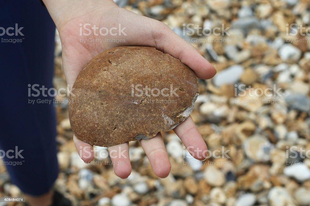 Ironstone nodule held in hand Hengistbury Dorset England stock photo