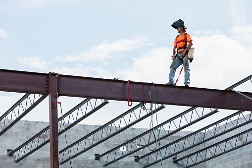 An Hispanic steel worker working high up on a girder. He is standing on the girder with wearing a welding helmet, working on attaching a roof joist to the girder.