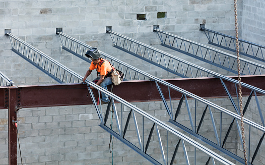 ✓ Ironworker at construction site installing roof joist Stock Photos