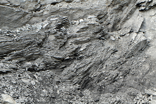 A very rough and irregular surface of a rock at a stone pit, the structured surface creates a wild and chaotic pattern or texture, resembling shale or granite.
