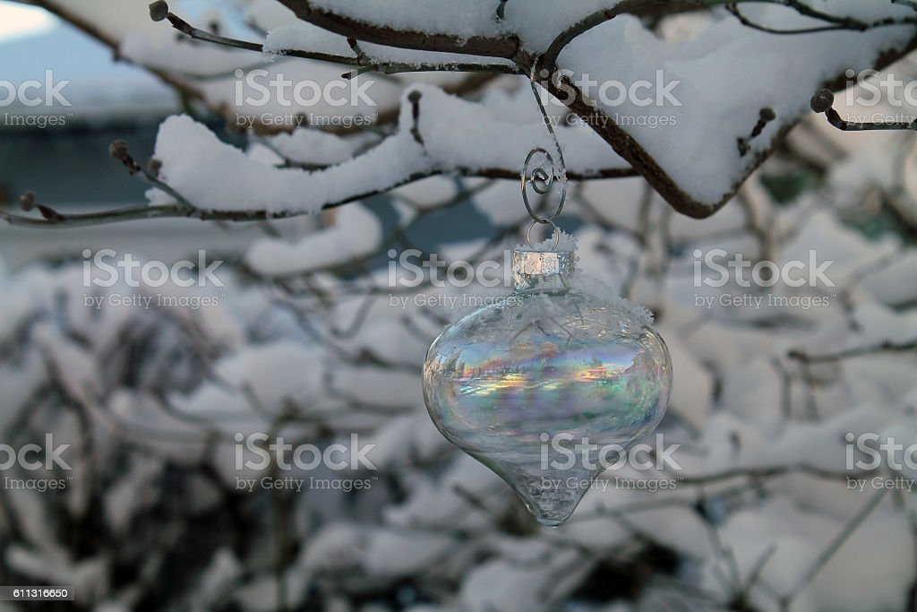 Irridescent Glass Christmas Ornament Hanging on a Snow-Covered Tree Branch stock photo