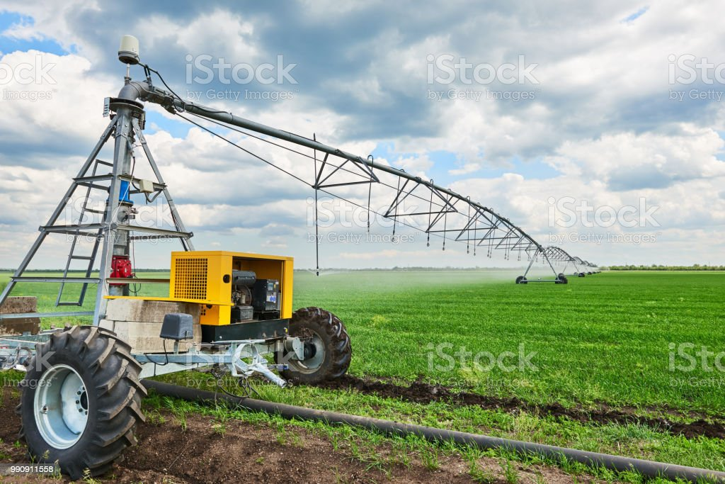 irrigation machine watering agricultural field with young sprouts, green plants on black soil and beautiful sky stock photo