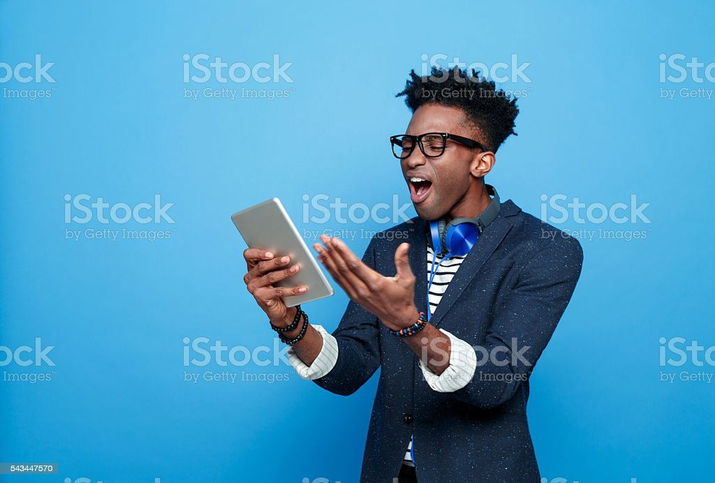 Irritated afro american guy using a digital tablet Studio portrait of angry afro american young man wearing striped top, navy blue jacket, nerd glasses and headphone, using a digital tablet. Studio portrait, blue background. Adult Stock Photo