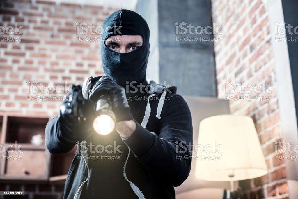 Ladrão mascarado irritado, segurando uma tocha - foto de acervo