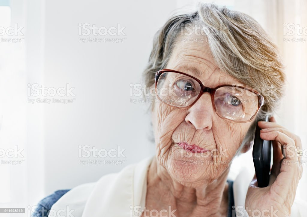 Irritated old woman listening to message on mobile phone stock photo