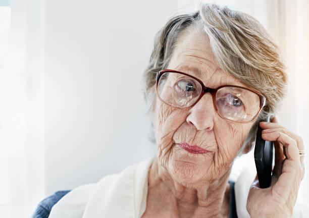 irrité de vieille femme écoute de message sur téléphone mobile - seulement des femmes seniors photos et images de collection