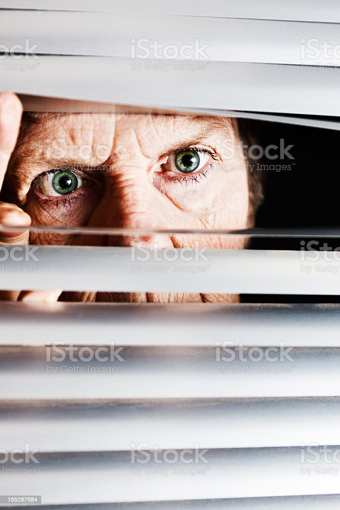 Irritated old woman looks though blinds angrily stock photo