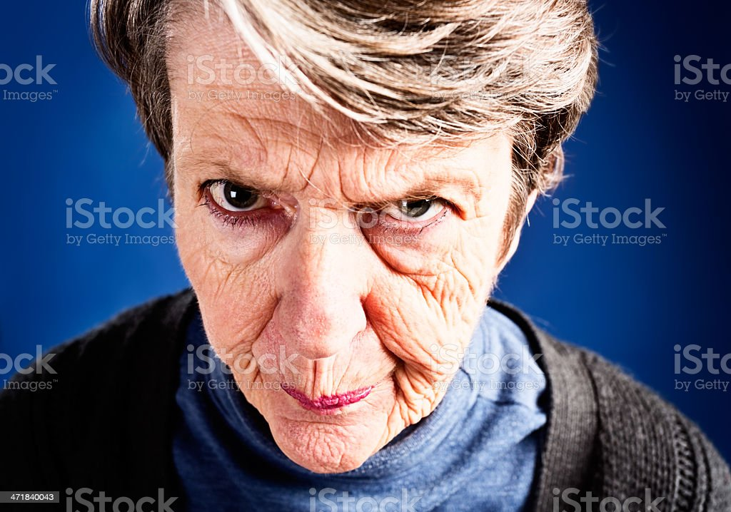 Irritated old woman purses lips and raises one eyebrow, frowning stock photo