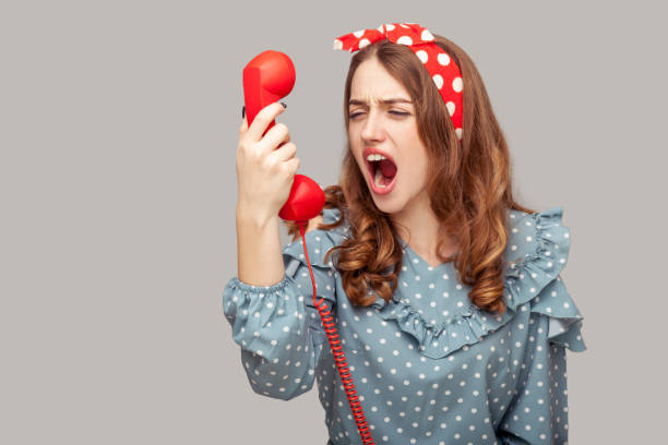 Irritated pinup girl shouting into phone handset, yelling scolding annoyed by telephone conversation, bad connection stock photo