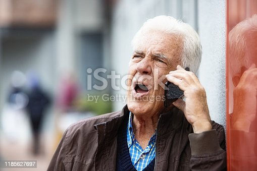 661896674istockphoto Irritated senior man talking on phone in street 1185627697