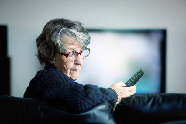 gereizte senior frau schlachten, tv-fernbedienung zu verwenden - alte serien stock-fotos und bilder