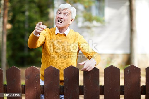 Angry senior man in yellow pullover standing by fence and pointing at you with annoyed expression