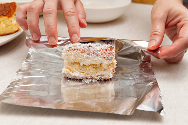 BOLO GELADO is a traditional Brazilian cake - Wrapping the cake with coconut sprinkles in aluminum foil. Front view BOLO GELADO is a traditional Brazilian cake - Wrapping the cake with coconut sprinkles in aluminum foil. Front view. gelado stock pictures, royalty-free photos & images