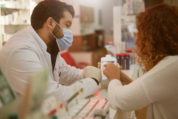 COVID-19 ist üblich, wenn der Apotheker dem Kunden den Handdesinfektionsmittel saniert. – Foto