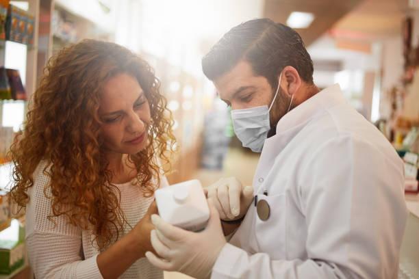 COVID-19 ist üblich, wenn der Apotheker dem Kunden den Handdesinfektionsmittel – Foto
