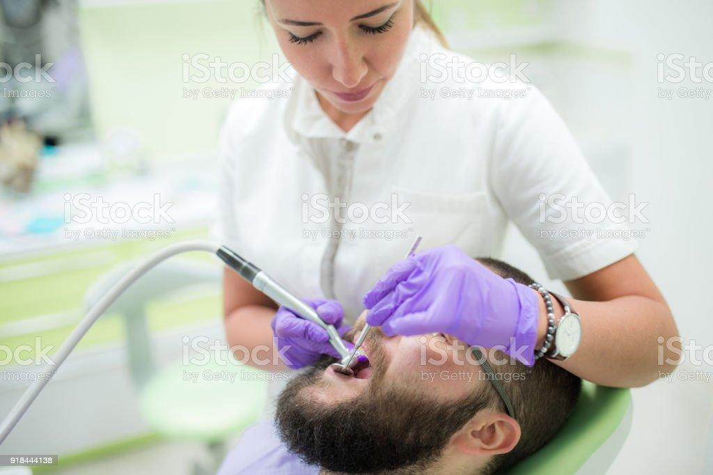 Female Dentist Repairing Young Man\'s Teeth