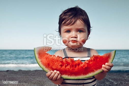 funny little girl on the beach eating watermelon and making funny face.