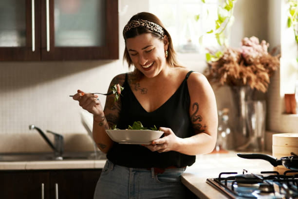 Is it really a diet if it tastes so good? Shot of a young woman eating a healthy salad at home dieting stock pictures, royalty-free photos & images