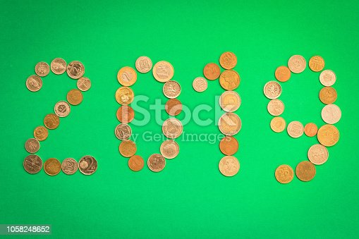 istock 2019 is laid out of various coins on a green background. New year's eve concept 1058248652