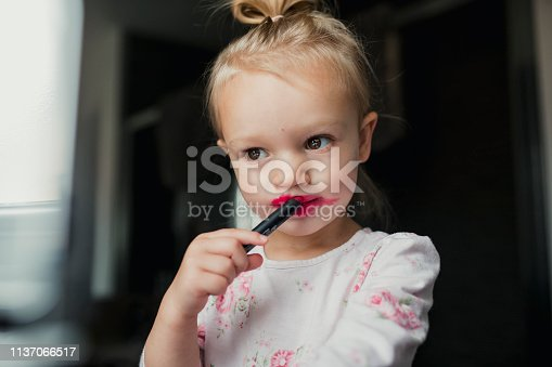 A close up shot of a young girl playing with lipstick, the pink is smudged around her mouth.