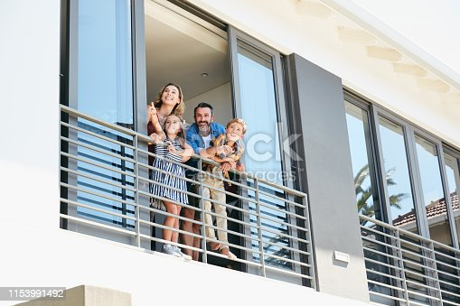 Shot of a happy young family standing on the balcony of their home